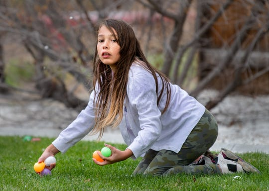 Melissa Yokoi, 10, of Fernley, gathers handfuls of eggs at Crosswinds Church.
