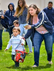 Parents rush to keep up with their kids at the start of the Easter egg hunt.