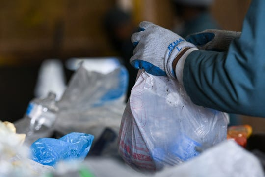 """Inmates sort plastic recycling at the Wicomico recycling facility on Tuesday, March 26, 2019. They break and discard plastic bags as they come across the conveyor belt. """"Grocery store bags are the bane of any landfill,"""" said recycling coordinator Jennifer Albero."""