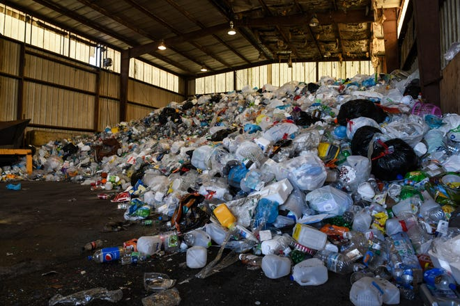 """A pile of plastic waits to be sorted at the Wicomico recycling center in Maryland in March 2019. It's dotted with plastic bags, although they aren't recyclable. """"Grocery store bags are the bane of any landfill,"""" said recycling coordinator Jennifer Albero."""