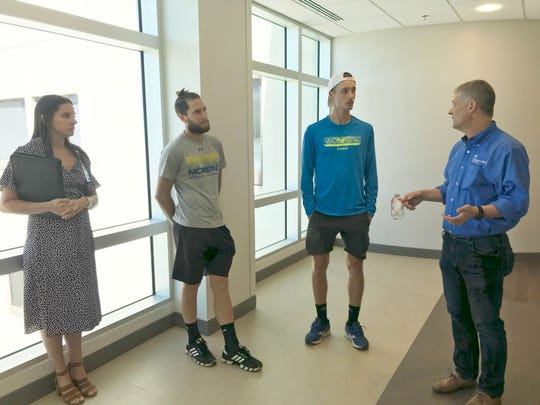 Dr. Christopher Rumana (right) discusses the layout of the family rooms and private bathrooms during a tour of the Vogter Neuro Intensive Care Unit with tennis players Marc Polmans (blue shirt), Hunter Reese and TMH communications strategist, Anna Saunders.