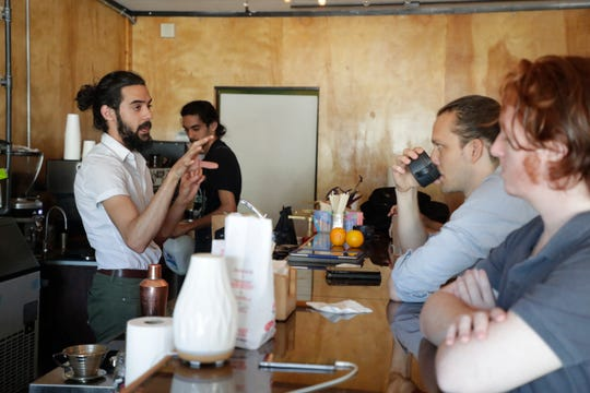 Michael Nazareth, co-owner of Serenity Coffee and Kava, talks with his mid-day customers at the popular All Saints neighborhood coffee shop, while construction on The Freight Yard, a new housing development, continues behind the business Monday, April 22, 2019.