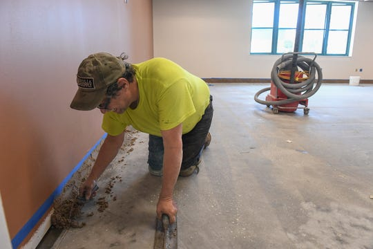 Robert Hensel, of Plexi-Chemie Inc, starts work on a high performance seamless epoxy flooring being installed in one of eight new classrooms on Wednesday, April 17, 2019, in the new 14,000-square-foot addition being built next to the existing campus at the Gifford Youth Achievement Center, which will be opened during a May 15 ribbon cutting.