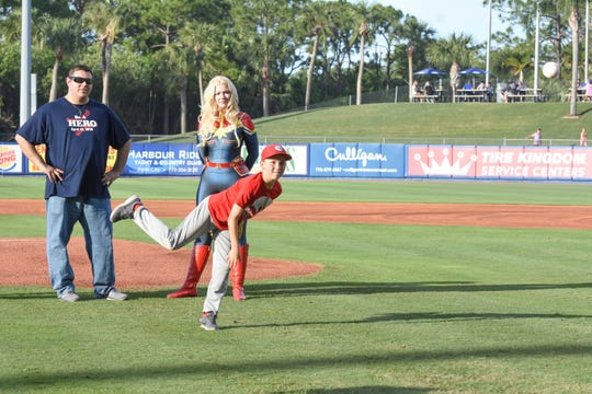 Paul Nigro, left, director at the Florida Guardian ad Litem and Captain Marvelous watch as Isaac throws the first pitch - a strike! - at First Data Field on April 13.