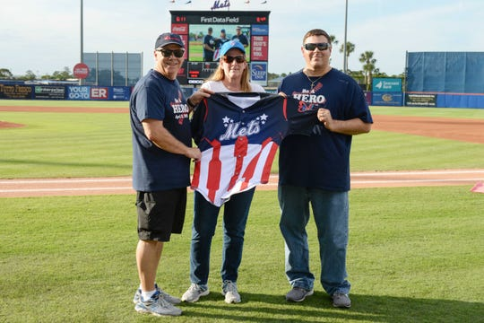 Evangeline Grissom Bruhn, center, receives a special St. Lucie Mets jersey from Voices for Children President Bob Perry, left, and Paul Nigro, director at the Florida Guardian ad Litem Program, for her ongoing support of children in dependency.