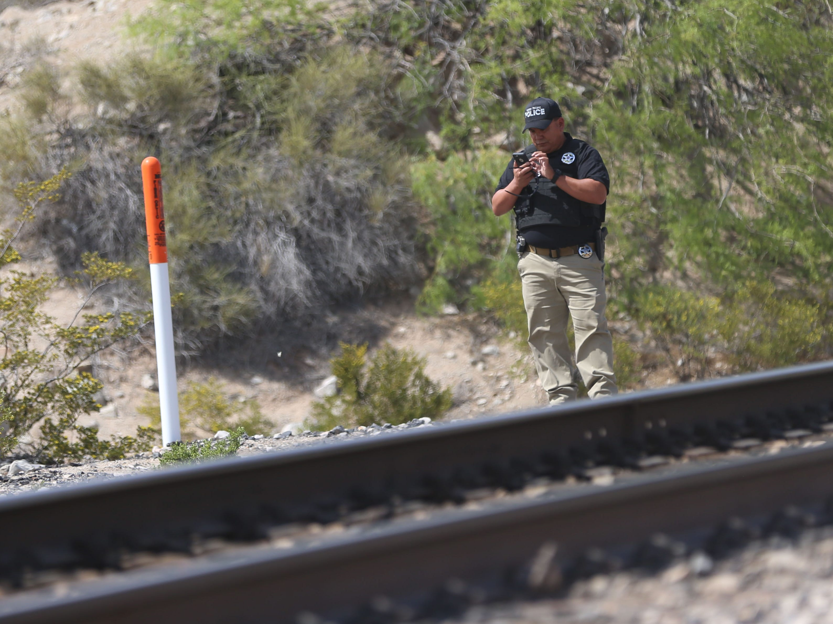 A Union Pacific Railroad police officer stands near the railroad tracks the United Constitutional Patriots - New Mexico Border Ops is located Monday, April 22, in Anapra, N.M. Sundland Park police and Union Pacific police say they will no longer be able to camp at their current site on Union Pacific property and will need to vacate by Friday.