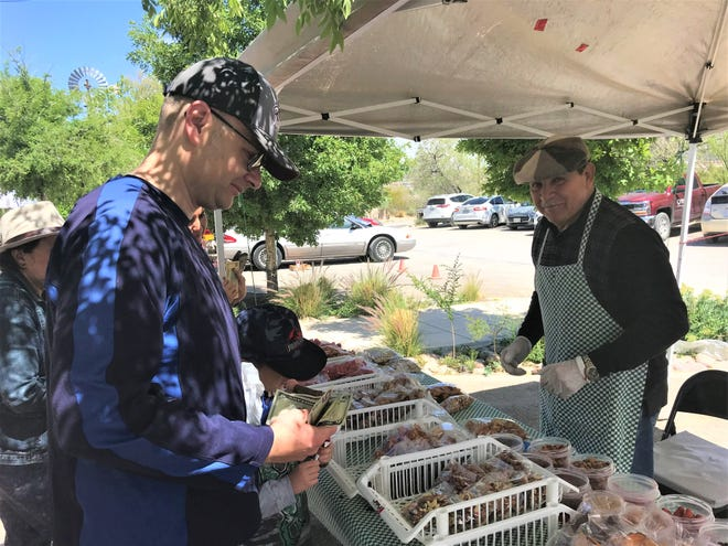 Bob Salcedo, owner of Mexican Delicious, helps a customer with his purchase of dehydrated sweet potato chips. Salcedo is one of several vendors at the Ardovino's farmers market.