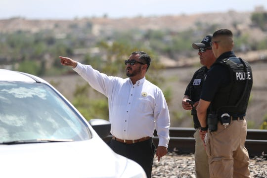 An El Paso City Works employee talks to Sunland Park police and Union Pacific police about where the United Constitutional Patriots - New Mexico Border Ops is located Monday, April 22, in Anapra, N.M. Sundland Park police and Union Pacific police say they will no longer be able to camp at their current site on Union Pacific property and will need to vacate by Friday.