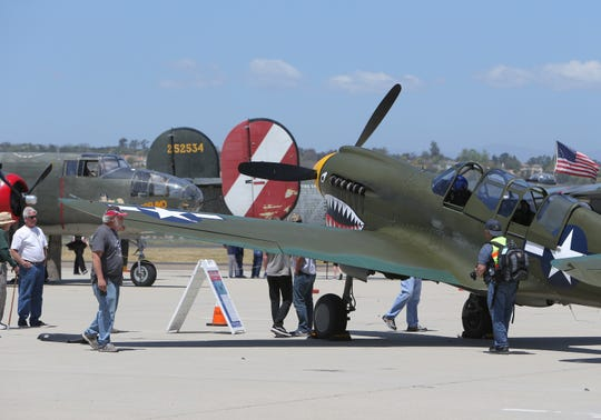 Guests look at the Curtiss P-40 that is on display during the Wings of Freedom Tour at the Camarillo Airport on Monday. The P-40 is one of five WWII planes that will be on display until Thursday.