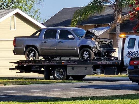 A truck is towed from the backyard of a Visalia home after crashing through a fence on Sunday, April 21, 2019.