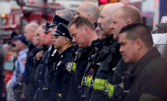 Members of the New York City Fire Department and New York City Police Department stand outside the Joseph Lucchese Funeral Home in the Bronx April 21, 2019 as the hearse containing  the body of FDNY member and U.S. Marine Christopher Slutman arrives. Slutman was killed last week by a roadside bomb in Afghanistan. His body was transported from Dover Air Force Base in Delaware by a military and fire department procession.