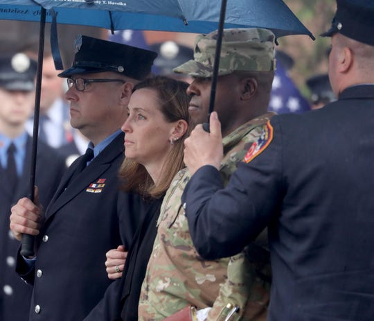 Shannon Slutman, the wife of FDNY member and U.S. Marine Christopher Slutman watches as her husband's casket is carried into the Joseph Lucchese Funeral Home in the Bronx April 21, 2019. Slutman was killed last week by a roadside bomb in Afghanistan. His body was transported from Dover Air Force Base in Delaware by a military and fire department procession.