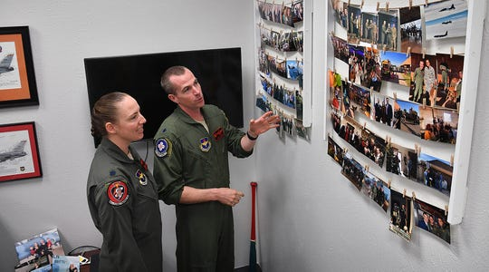 Lt. Col. Elia Hickie and her husband, Lt. Col. Mark Hickie, look over photos of previous military assignments hanging in Mark's office. The couple are the first husband and wife squadron commanders at Sheppard Air Force Base.