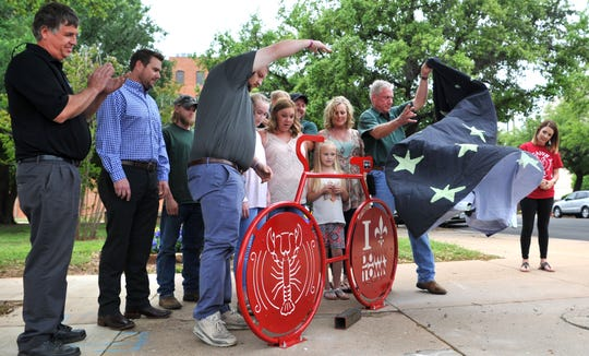 Employees and family members from Brian's Plumbing and Fisher 59 helped unveil the latest Downtown Wichita Falls Development project Monday morning. The  Cajun Fest bike rack at the Bud Daniel Park is the latest DWFD bike rack project.