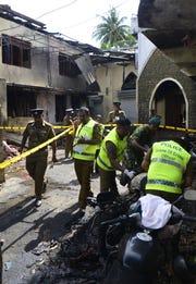 Sri Lankan security personnel and police investigators look through debris outside Zion Church on April 21, 2019 following an explosion in Batticaloa, Sri Lanka.