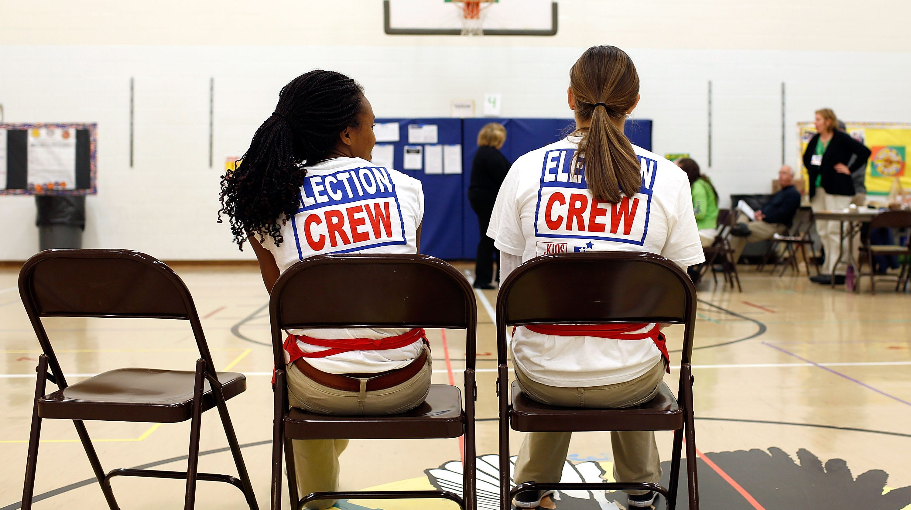 Kaylee Taylor (left) and Amber Taylor (no relation), both 17 and of Dublin, Ohio, wait to assist voters voting at the Wyandot Elementary School in Dublin, Ohio on Tuesday, November 6, 2012. Both girls were working for Youth at the Booth, a program that allows high school seniors to work at polling stations and gives them an opportunity to be involved in the polling process.