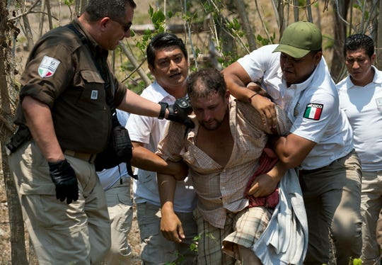 A Central American migrant is detained by Mexican immigration agents on the highway to Pijijiapan, Mexico, Monday, April 22, 2019. Mexican police and immigration agents detained hundreds of Central American migrants Monday in the largest single raid on a migrant caravan since the groups started moving through Mexico last year.