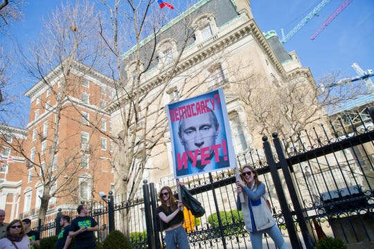 Protesters hold up a sign showing Russian President Vladimir Putin in front of the Russian ambassador's residence in Washington in 2017.