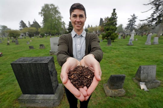 "In this Friday, April 19, 2019, photo Katrina Spade, the founder and CEO of Recompose, displays a sample of the compost material left from the decomposition of a cow, using a combination of wood chips, alfalfa and straw, as she poses in a cemetery in Seattle. Washington is set to become the first state to allow the burial alternative known as ""natural organic reduction,"" that turns a body into soil in a matter of weeks."