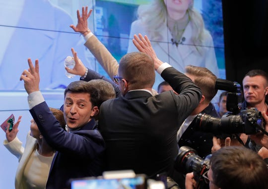 In this Sunday, April 21, 2019, photo, Ukrainian comedian and presidential candidate Volodymyr Zelenskiy, left, makes the victory sign after seeing the exit polls for the second round of presidential elections in Kiev, Ukraine. Ukrainians voted on Sunday in a presidential runoff as the nation's incumbent leader struggles to fend off a strong challenge by a comedian who denounces corruption and plays the role of president in a TV sitcom.