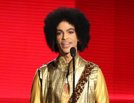 """FILE - In this Nov. 22, 2015, file photo, Prince presents the award for favorite album - Soul/R&B at the American Music Awards in Los Angeles. The memoir Prince was working on at the time of his death, """"The Beautiful Ones,"""" is due out in late October 2019. (Photo by Matt Sayles/Invision/AP, File) ORG XMIT: NYSB773"""
