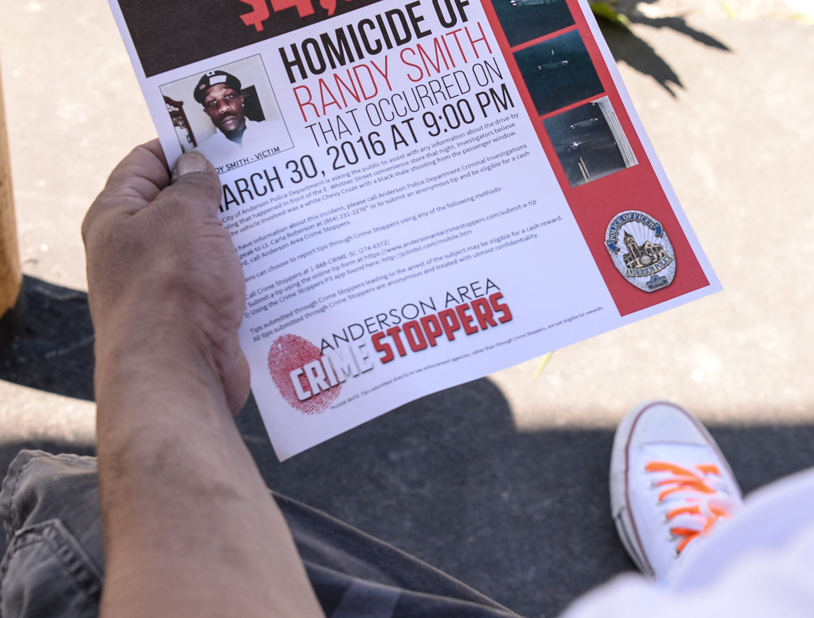 James Smith, father of Randy Smith, looks at a Crime Stopper flyer after a press conference asking the public for tips in the cold case homicide case of Randy Smith, who was shot in a drive-by shooting in March 2016.
