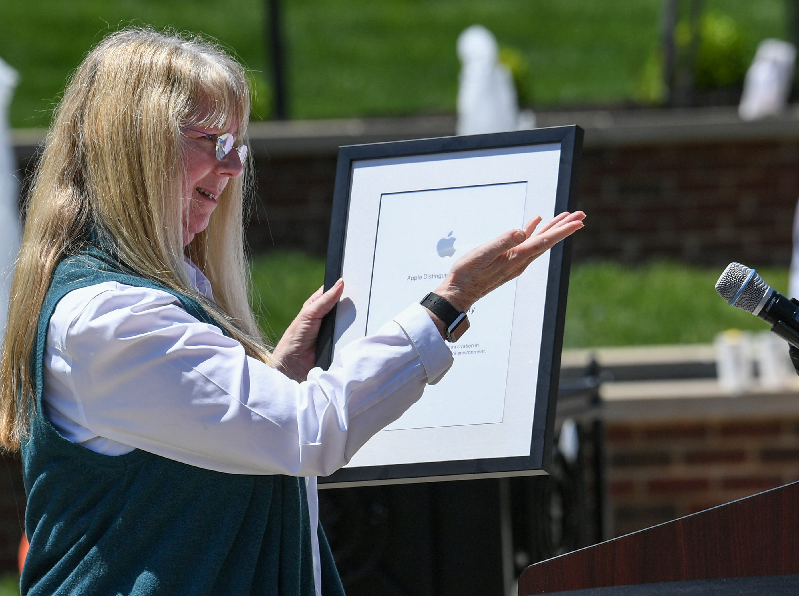 Anne Van Middlesworth, a National Higher Education Market Development Manager for Apple at the Apple Distinguished School award event in front of the G. Ross Anderson Student Center at Anderson University in Anderson Tuesday. President Evans Whitaker accepted the certificate from Anne Van Middlesworth, a National Higher Education Development Manager for Apple before two hundred students, faculty and guests. It was the third time receiving the distinction since the school started a digital learning initiative in 2011.