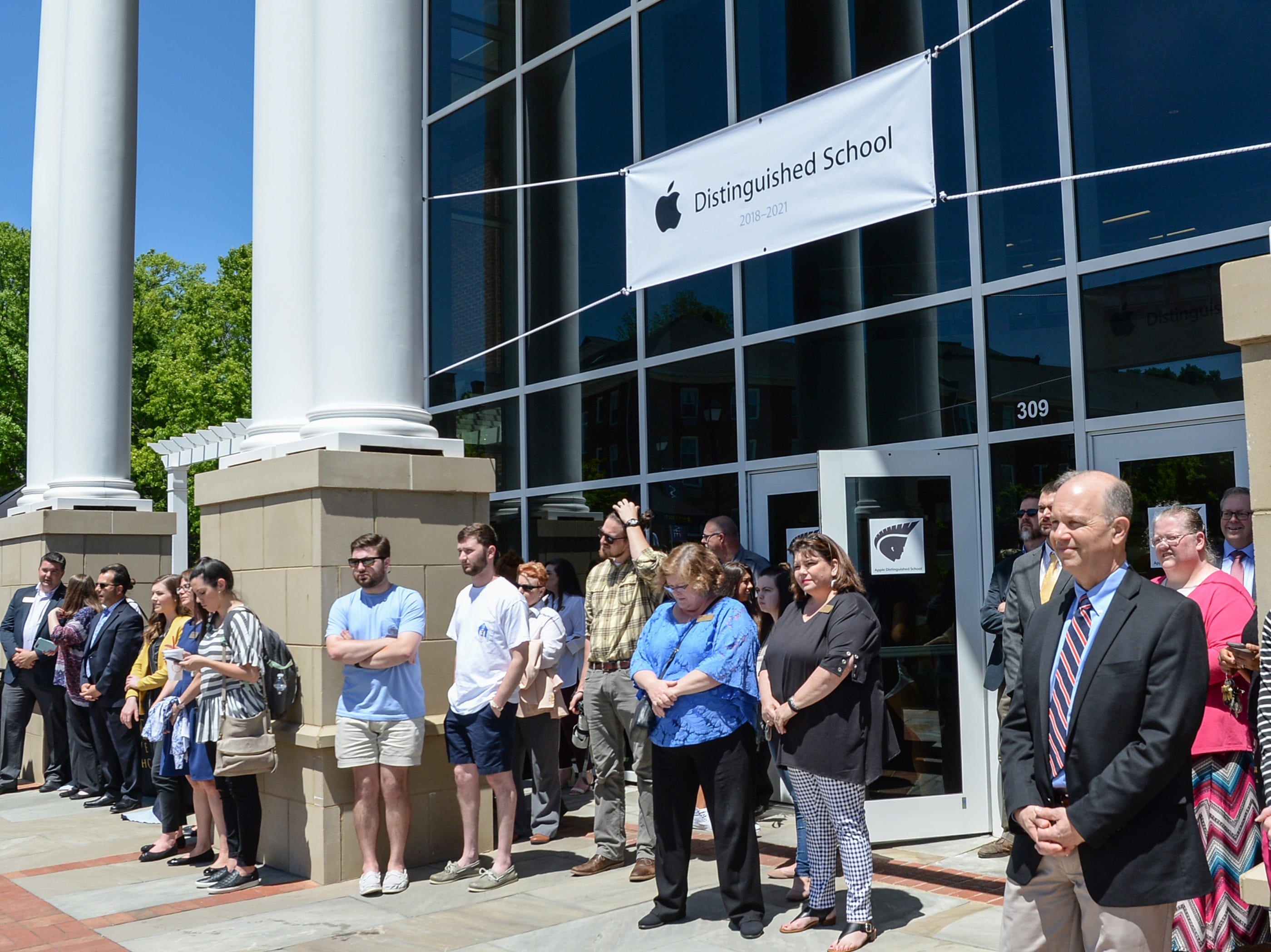 Students and faculty watch as Anne Van Middlesworth, a National Higher Education Market Development Manager for Apple presents the Apple Distinguished School award to President Evans Whitaker at the event in front of the G. Ross Anderson Student Center at Anderson University in Anderson Tuesday. It was the third time receiving the distinction since the school started a digital learning initiative in 2011.