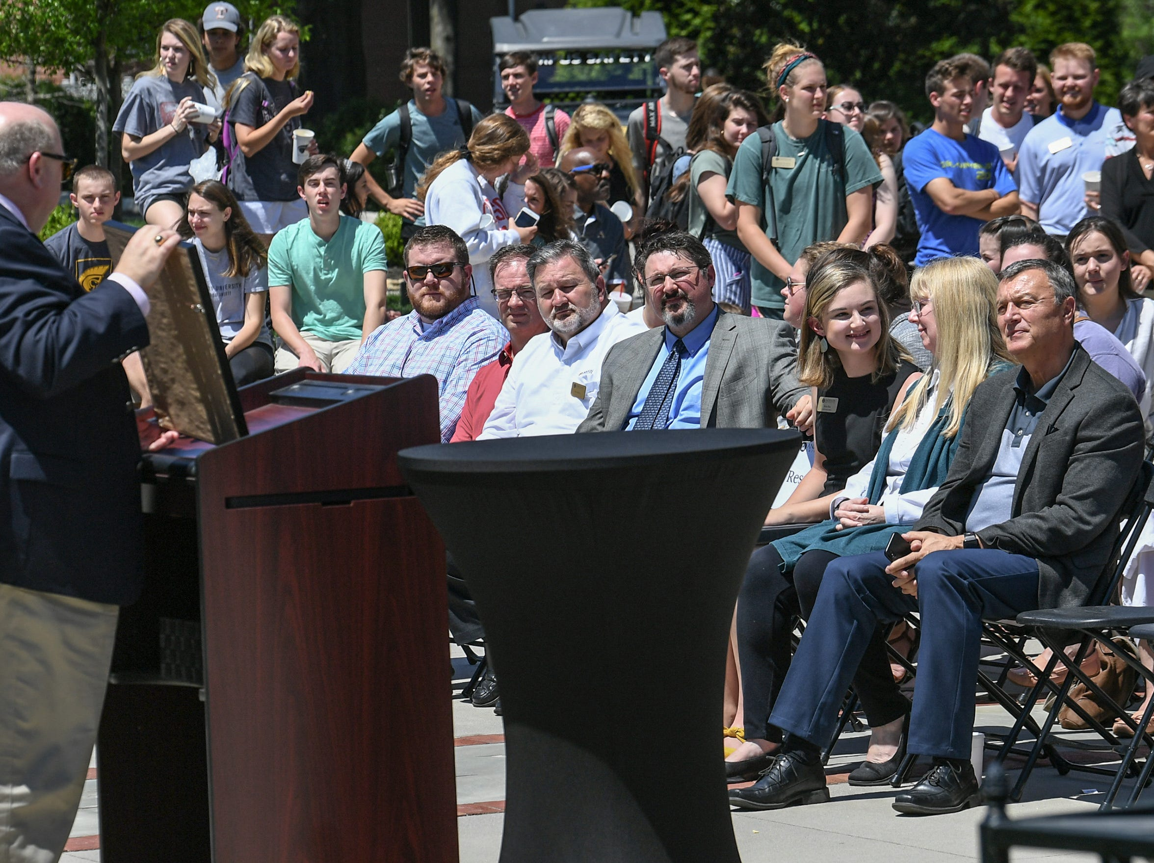 President Evans Whitaker holds The Apple Distinguished School award at the event in front of the G. Ross Anderson Student Center at Anderson University in Anderson Tuesday. It was the third time receiving the distinction since the school started a digital learning initiative in 2011.