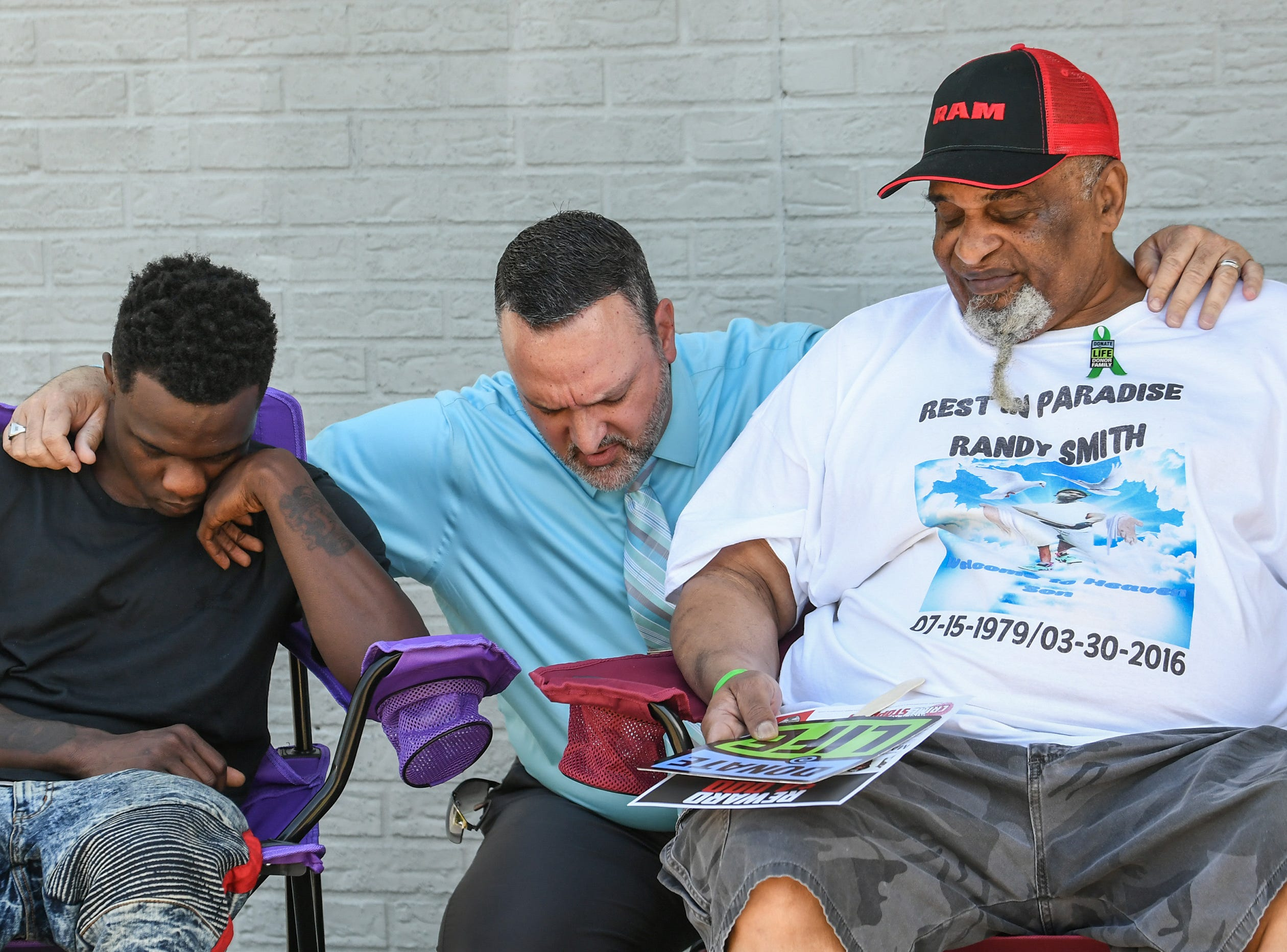 Stephen Combs, middle, Anderson Area Crime Stoppers President, prays with Montrell Jones, left, son of the late Randy Smith, and father James Smith, right, after a press conference asking the public for tips in the cold case homicide case. Randy Smith was shot in a drive-by shooting in March 2016.