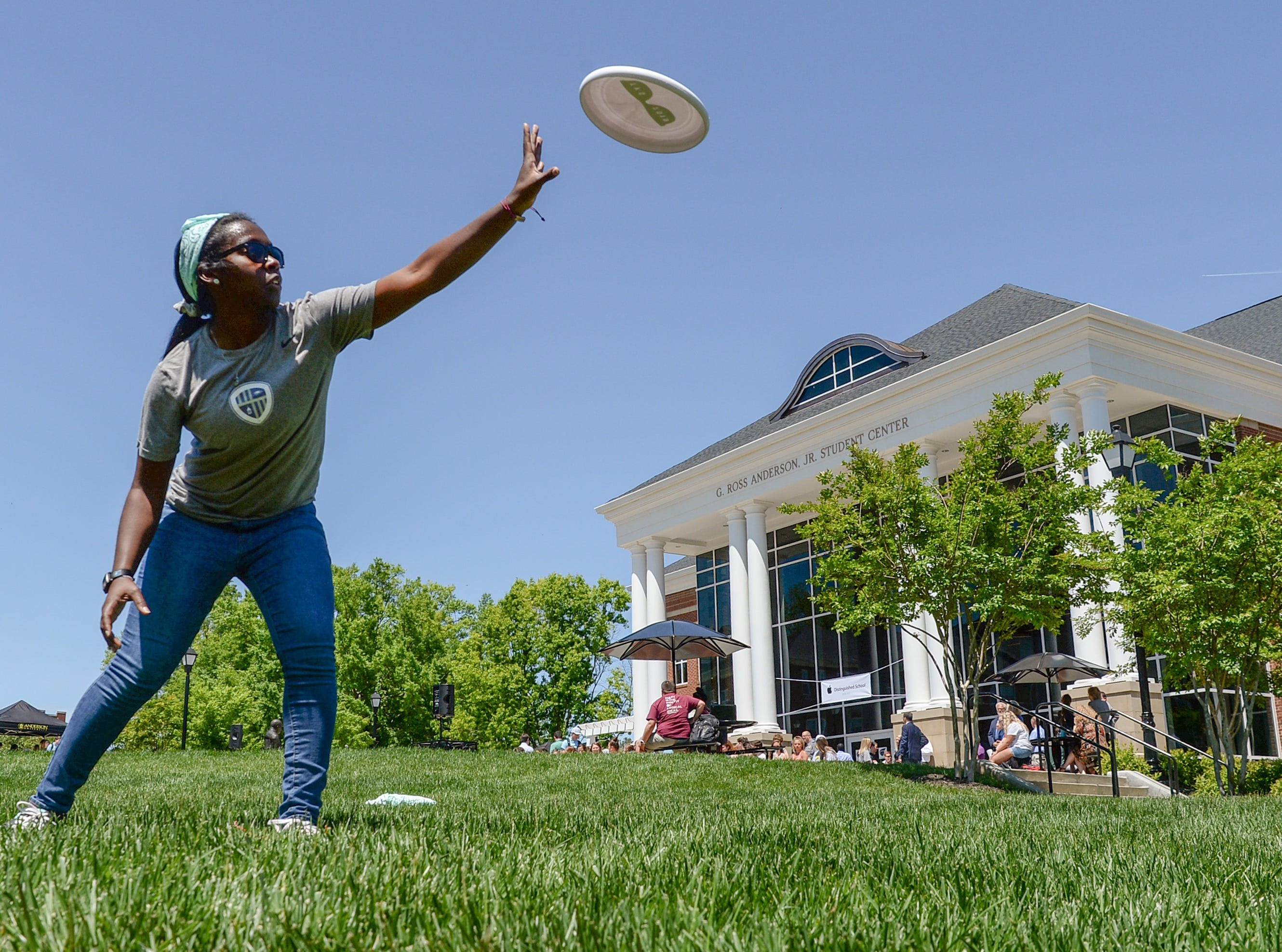 Tiffany Cooley, a sophomore Kinesiology major at Anderson University, catches a plastic flying disc minutes before the school was presented an Apple Distinguished School award at a certificate presentation ceremony in front of the G. Ross Anderson Student Center at Anderson University in Anderson Tuesday. President Evans Whitaker accepted the certificate from Anne Van Middlesworth, a National Higher Education Development Manager for Apple before two hundred students, faculty and guests. It was the third time receiving the distinction since the school started a digital learning initiative in 2011.