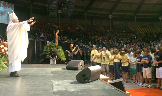 The late Bishop Ronald Herzog (left) of the Diocese of Alexandria blesses young adults attending Steubenville South in 2011.