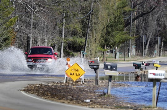 A motorists drives though water that covers State 187.