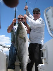 Steve Ondrof (left) and Dave Flood with a 42-pound striped bass caught on the Hi Flier charter boat.