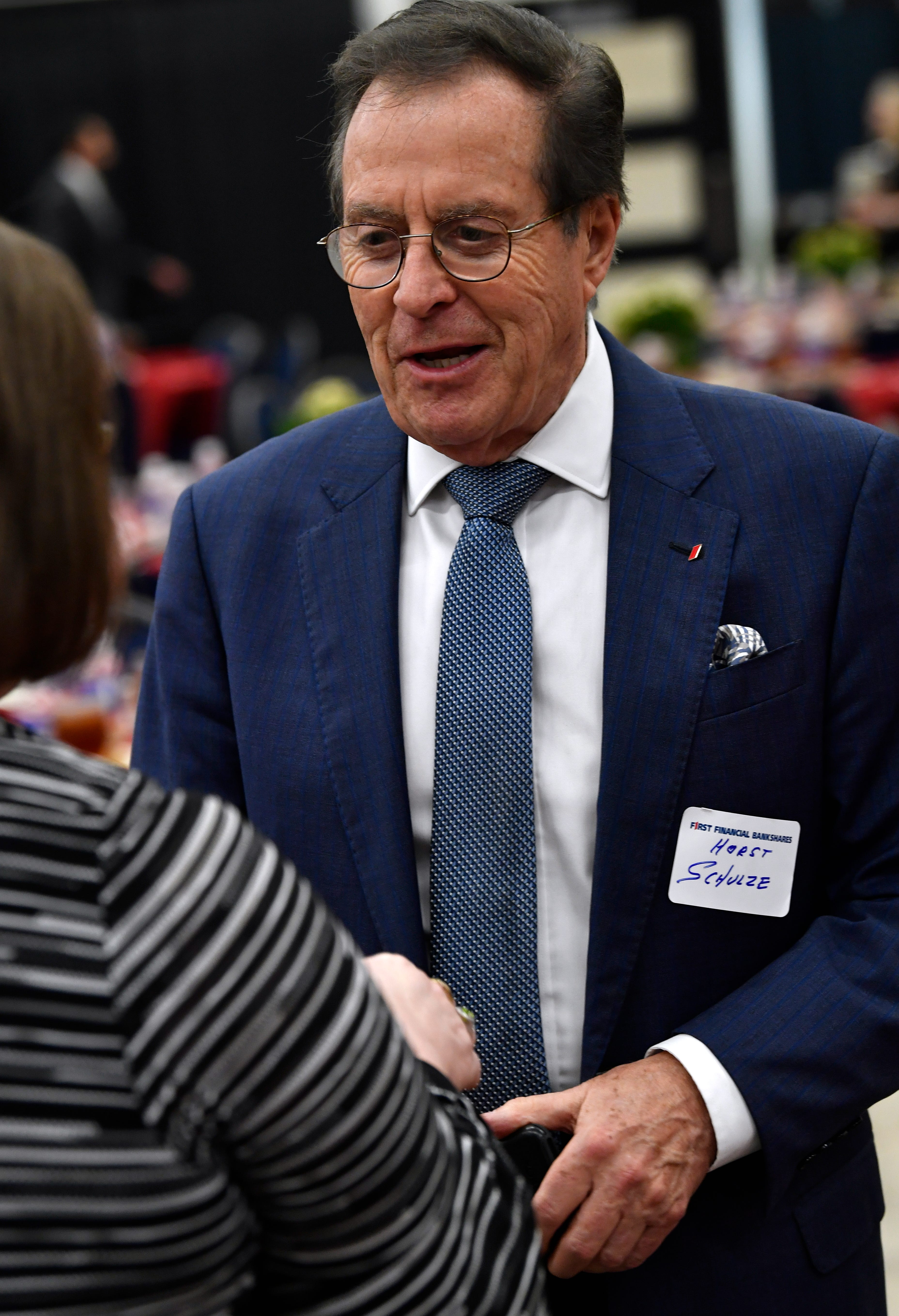 """Horst Schulze, the former president of Ritz-Carlton, greets an attendee at the luncheon after the First Financial Bankshares annual meeting Tuesday. Schulze has authored a book on customer service, """"Excellence Wins,"""" which was provided free to guests."""