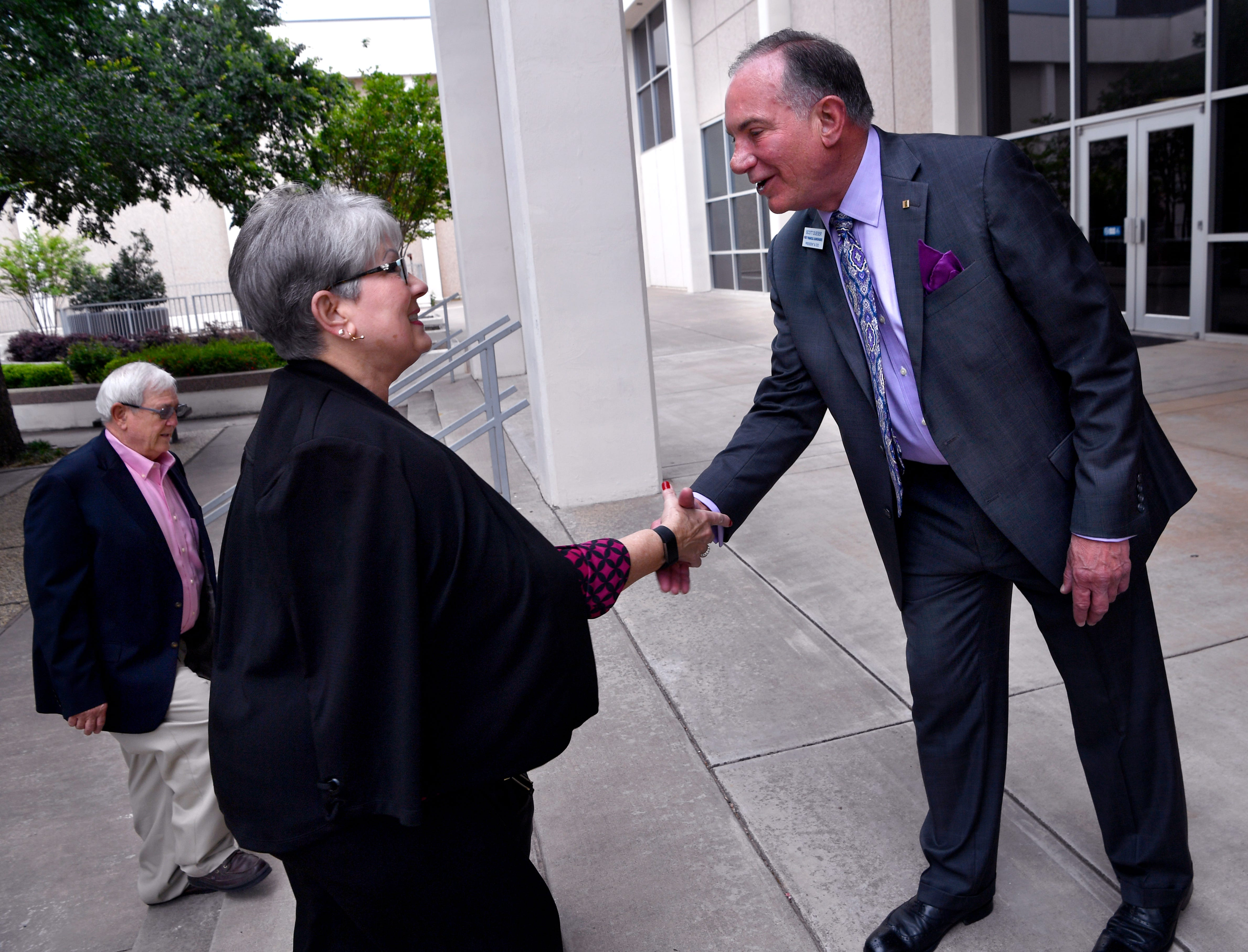 Scott Dueser greets Nancy Baker and her husband Wayne prior to Tuesday's annual shareholder meeting Tuesday. Dueser is the chairman, president and chief executive officer of First Financial Bankshares,