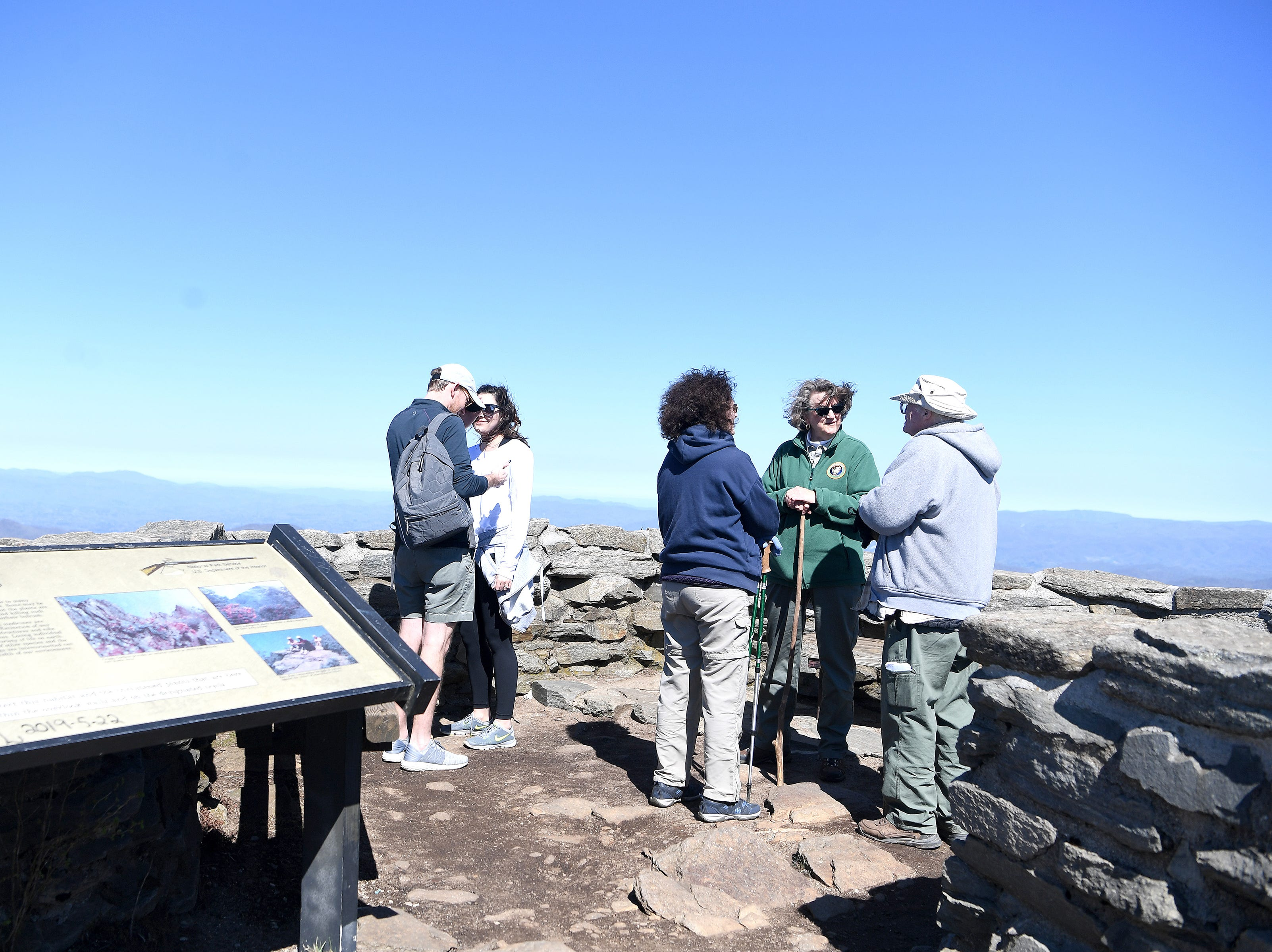 Friends of the Blue Ridge Parkway co-chair Nancy Midgette, center right, answers questions from Claire and Dave Davis, of West Virginia, at the overlook of the Craggy Pinnacle trail on April 22, 2019.