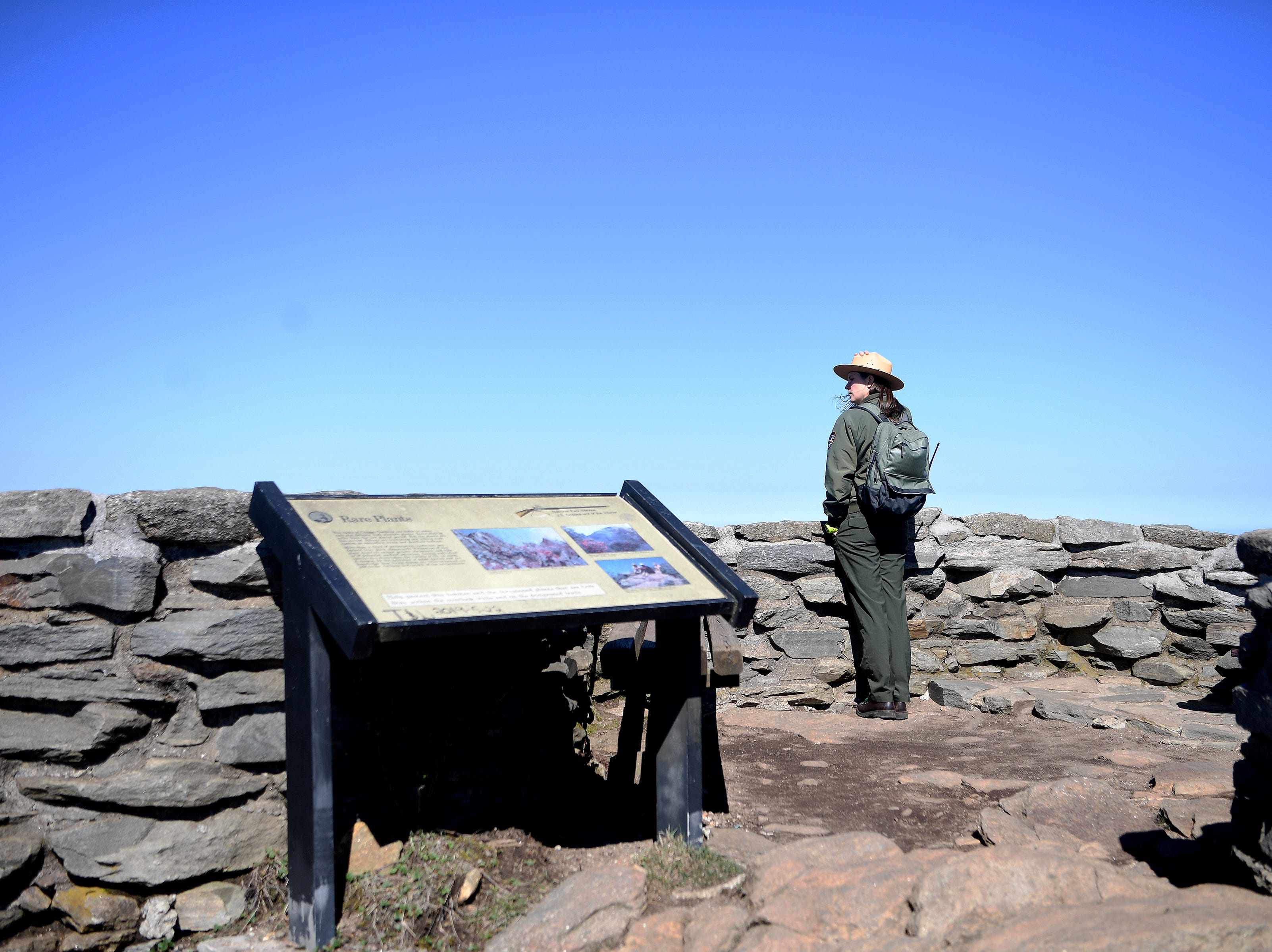 Blue Ridge Parkway spokesperson Caitlin Worth looks out at the view from the top of the Craggy Pinnacle Trail on the Blue Ridge Parkway after explaining the Craggy Rovers program on April 22, 2019. The program is run by volunteers that help answer questions for visitors and keep them on the trails to preserve the fragile and rare vegetation that grows in the area.