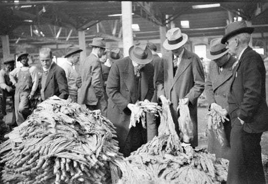 Buyers looking at tobacco in warehouse during auction sales, Durham, North Carolina, presumably November 1939. Library of Congress photo.