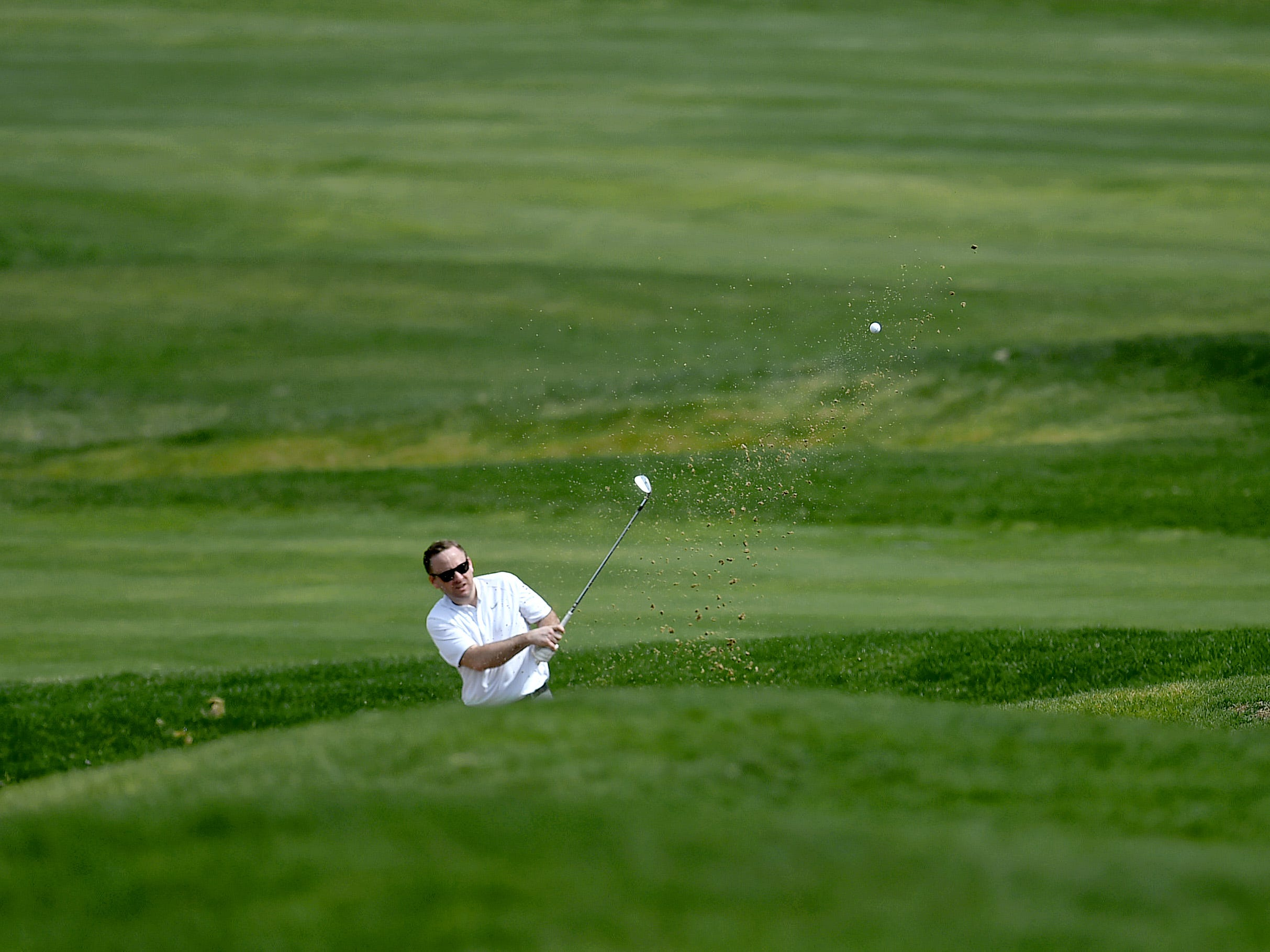 A golfer attempts to chip his way out of a sand trap at The Links at Hiawatha Landing in Apalachin on Tuesday, April 23, 2019.