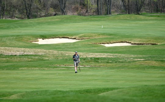 A golfer walks the greens at The Links at Hiawatha Landing on Tuesday, April 23, 2019.