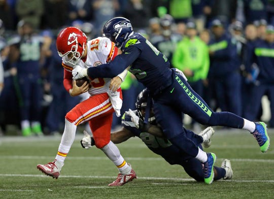 In this Dec. 23, 2018, file photo, Kansas City Chiefs quarterback Pat Mahomes is tackled by Seattle Seahawks defensive end Frank Clark. The Kansas City Chiefs have agreed to acquire defensive end Frank Clark from the Seattle Seahawks in exchange for a first-round draft pick this year and a second-round pick in 2020. Almost immediately after word leaked of the trade on Tuesday, April 23, 2019, Clark and the Chiefs worked quickly to reach agreement on a five-year contract worth up to $105 million, according to a person with knowledge of the deal. The person spoke to The Associated Press on the condition of anonymity because the deal had not been announced by either team and was still pending a physical.