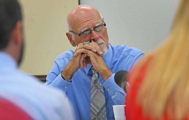 Magistrate Tom Young listened to arguments from the teachers union and school district at a meeting last month.