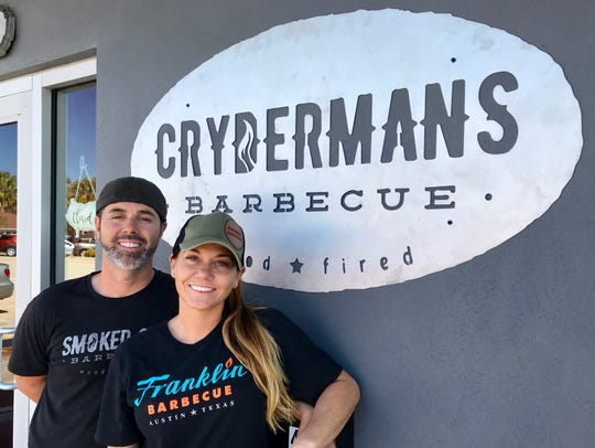 Chad and Amy Cryderman stand in front of their new Melbourne barbecue restaurant.