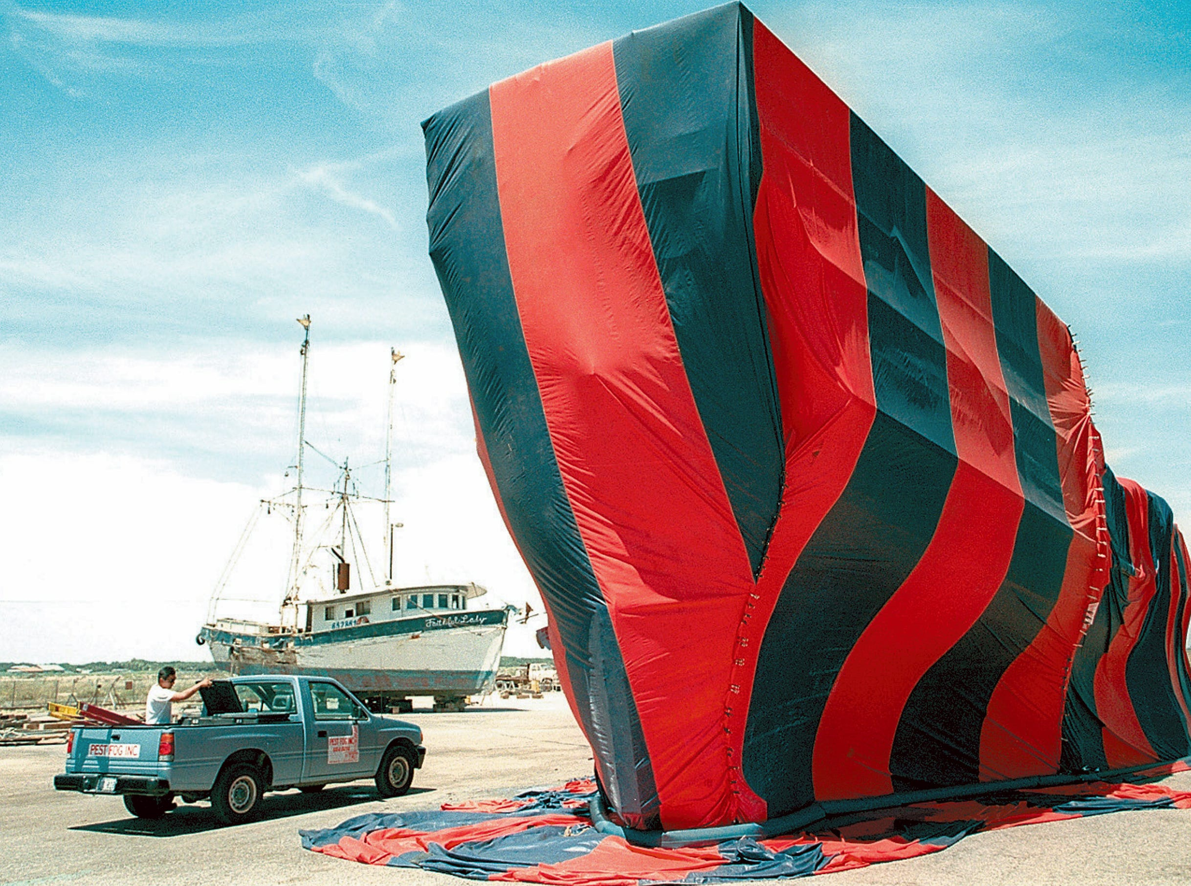 Andrew Trevino of Pest Fog Inc. watches guard over La Nina as it sits in the boatyard at Gulf Copper Ship Repair and Boatyard in Ingleside. The ship was tented and fumigated on Aug. 22, 1997.