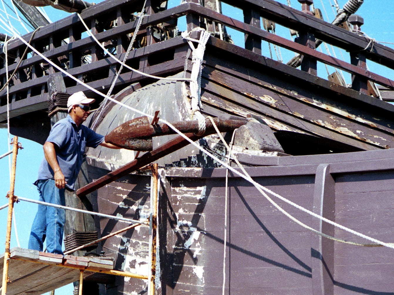Ruben Pena works on a scaffold as he prepares the Santa Maria for a new coat of paint in October 1999. The Columbus Fleet Association has a plan to keep the ships open for the next several months while it negotiates the ships' return to the Spanish government.