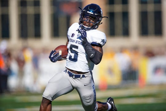 Utah State Aggies running back Darwin Thompson (5) runs for a touchdown against the Wyoming Cowboys during the first quarter at Jonah Field War Memorial Stadium.