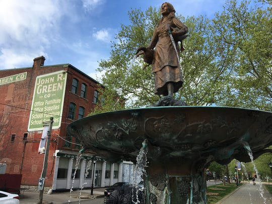 April 23, 2019: Waters of the Goose Girl Fountain flow in Covington's MainStrasse Village within sight of the John R. Green Co. building. The building at 411 W. 6th St. will be the site of 177 new John R. Lofts apartments scheduled to open in spring 2021.