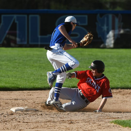 Andrew Kittell slides into second base beneath the tag of Zanesville's Avery Parmer on Monday at Jay Payton Field. Coshocton won, 5-4.