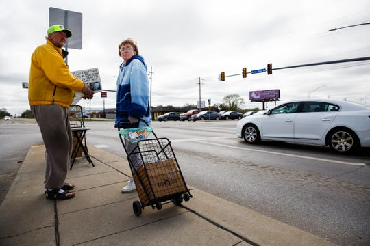 Dale Cummings and Ellen Hunt hold a sign asking for money to help with burial expenses for their dog Misty at the corner of SE 14th and Army Post Road on Tuesday, April 23, 2019, in Des Moines. Unable to have children of her own, Hunt got Misty 17 years ago and had her certified as a service dog to help her cope. Already facing financial hardships from a broken down vehicle, Hunt and her boyfriend Dale Cummings have been on the corner for help to get by. The city of Des Moines is banning panhandling on medians less than six feet wide for safety concerns.